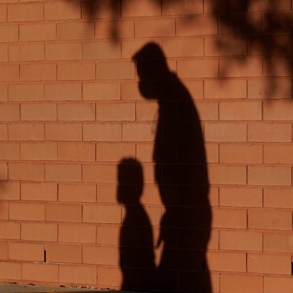 shadow of adult leading child