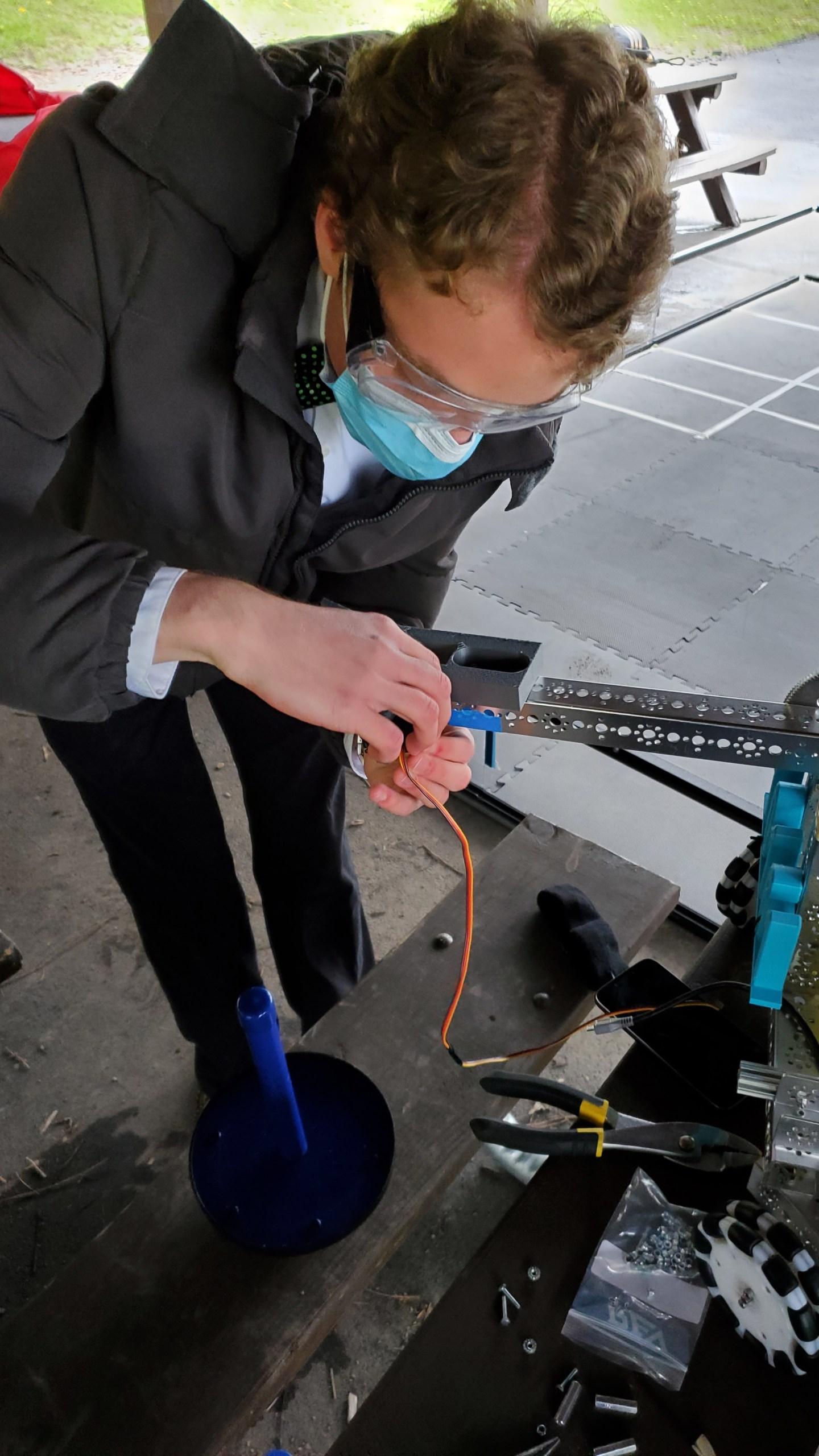 Isaiah Markle rewiring robot during outdoor meeting during Pandemic